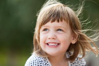 A girl smiles outside | Evansville IN children's dentistry