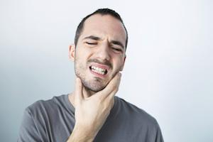 A man holds his jaw | Treatment for Bruxism and TMJ in McCutchanville