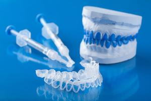 A set of whitening trays and gel on a blue backdrop | Evansville In-Office Teeth Whitening