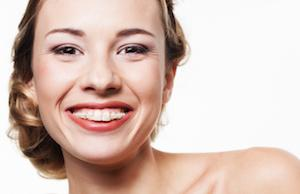 A woman with braces smiles in front of a white backdrop | Evansville IN six month smiles