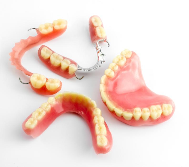 Dentures lay on a white backdrop | dentures Evansville iN