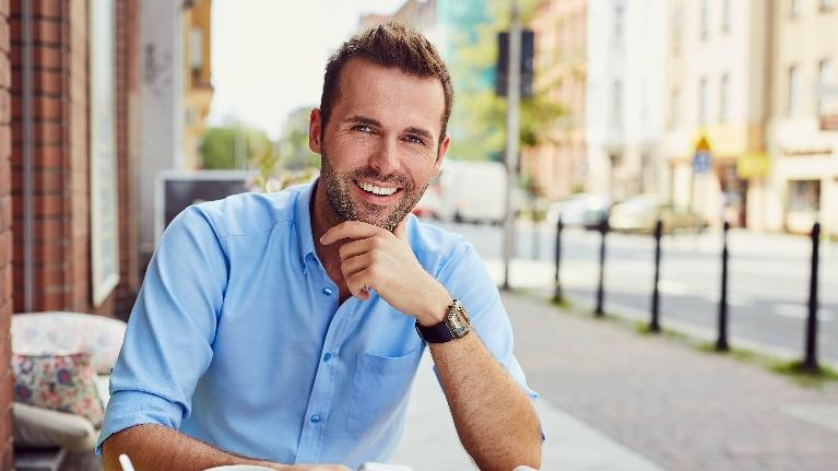 a man smiles at a café | cosmetic dentist evansville