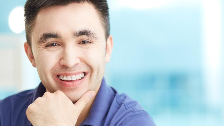 A man with braces smiles | Six month smiles evansville