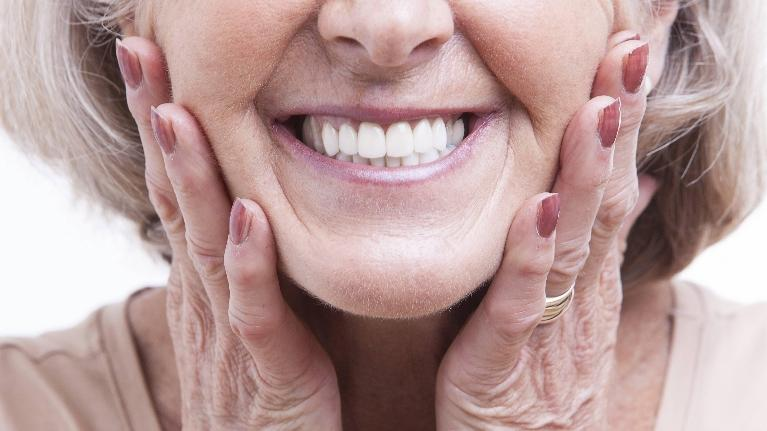 a closeup of an older woman smiling | dental implants evansville