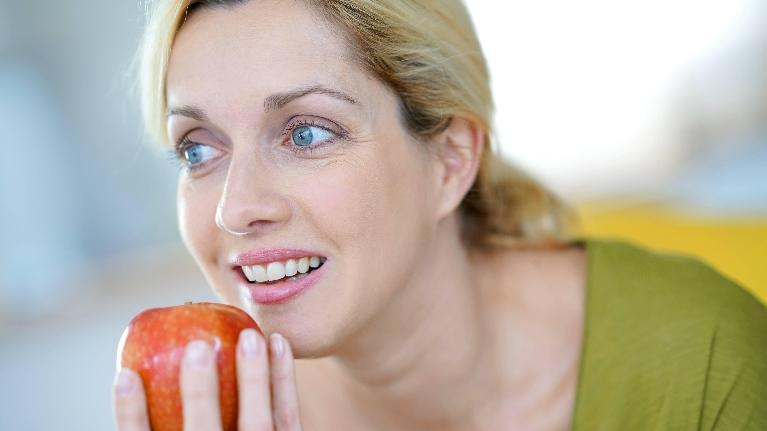 a woman about to take a bite of an apple | tmj dentist evansville in