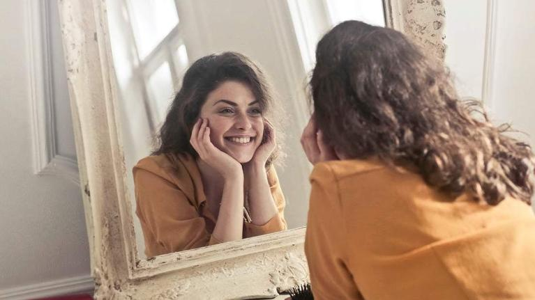 A woman smiles in a mirror | Cosmetic Dentist Evansville IN