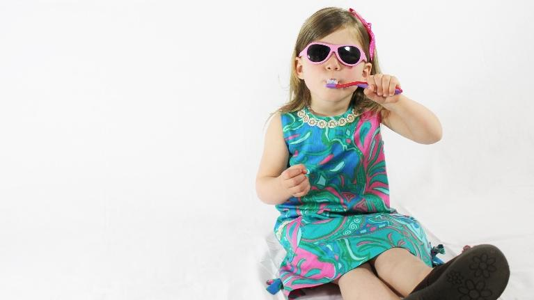 a girl wearing sunglasses brushes her teeth | childrens dentist evansville in