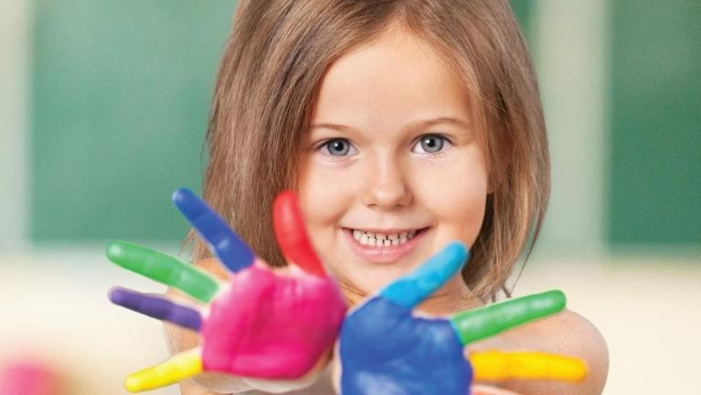 young girl smiling while showing off hands with multi-colored paint on them